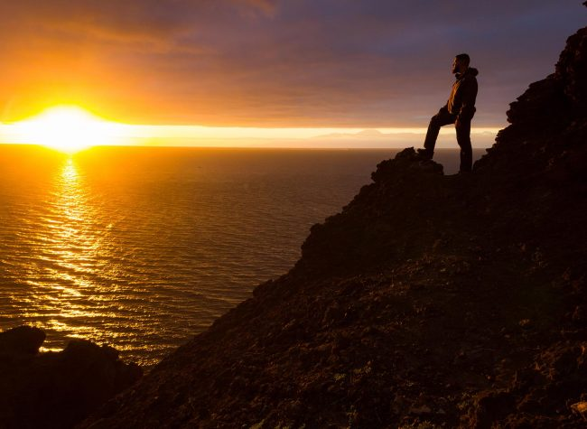 Lonely man standing on cliff edge rock staring at sunset with Te