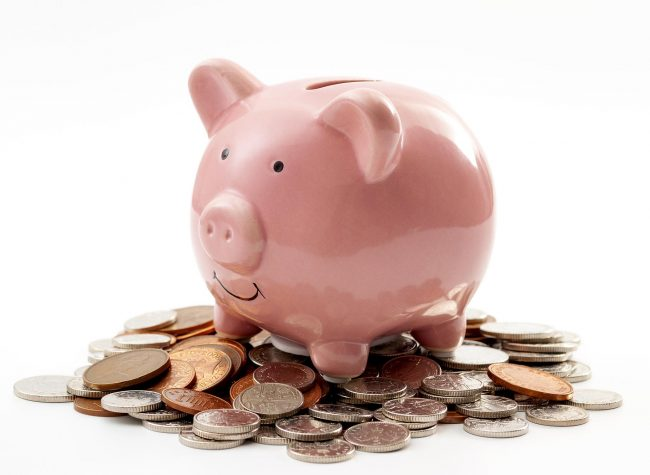 Save money, financial planning of personal finances and being thrifty concept theme with a pink piggy bank sitting on a pile of bronze and silver colored coins isolated on white background