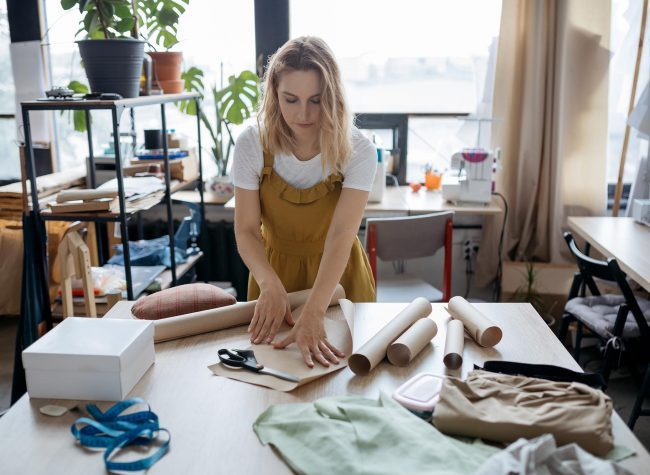 Female tailor working with paper patterns. Small business and se