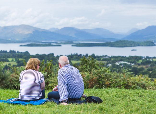 Enderly couple enjoy beautiful panoramic view of Trossachs landscape, Scotland. High quality photo