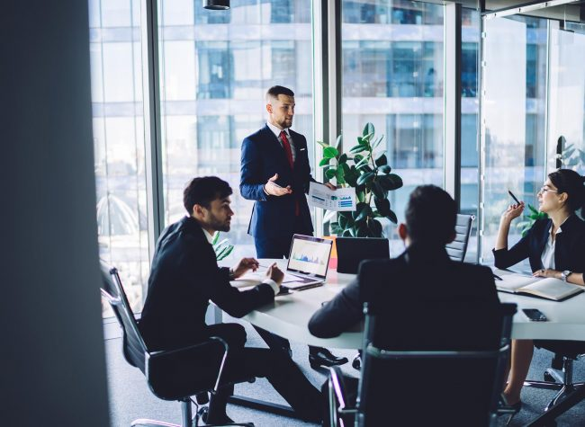 Confident successful businessman in formal black suit standing next to colleagues and analyzing financial report during conference in modern workspace