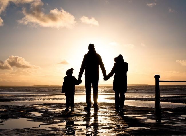Silhouette of two adults and a child at the coast